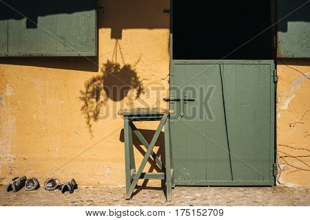 Empty stable for horses with green door and yellow wall on ranch