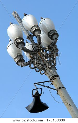 Vintage lamppost with loudspeaker on blue sky background