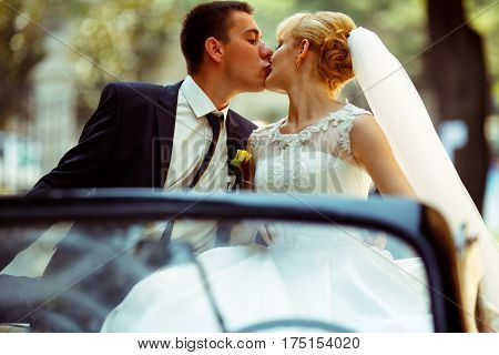 Fiance Kisses Pretty Blonde Bride Sitting On A Black Cabriolet