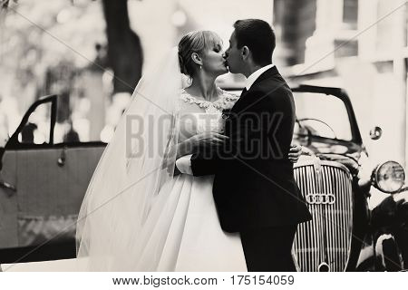 Black And White Photograph Of A Wedding Couple Kissing Behind A Retro Car