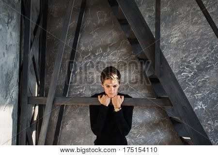 A young emotion guy in a black shirt with a clock on the hand in the dark room with natural light. Emotional portrait. Bright display of emotion. Conceptual photography. The talented actor with emotion.