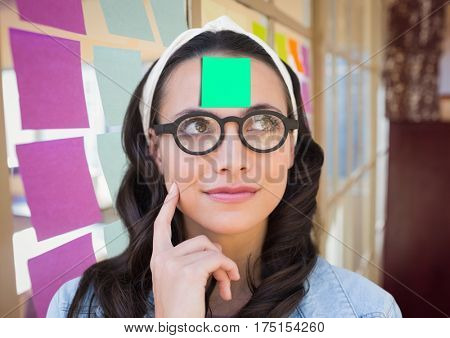 Thoughtful woman with sticky note on her forehead