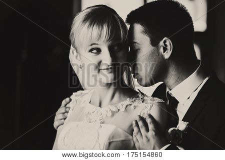 A Balck And White Picture Of Smiling Bride And Groom Holding Her Shoulders Tenderly