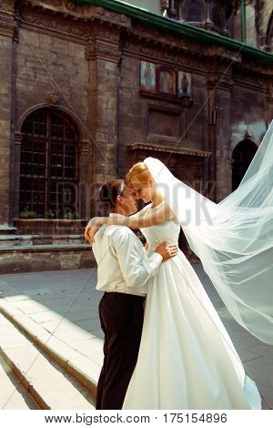 Fiance Holds Bride's Waist Tenderly While She Stands On Footsteps Behind An Old Cathedral