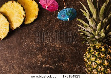 Ripe tropical pineapple and cocktail umbrellas on a dark table with a marble texture with scratches. Cut fruit. Healthy tropical eating. Going on a journey to the south.