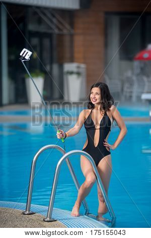 Smiling Girl In A Black Sexy Swimsuit Posing Against Swimming Pool Makes Selfie Photo With Monopod O