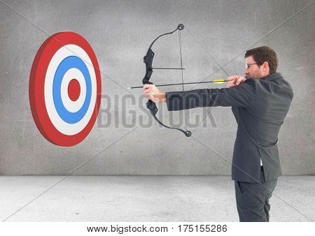 Businessman aiming at target with bow and arrow against grey background