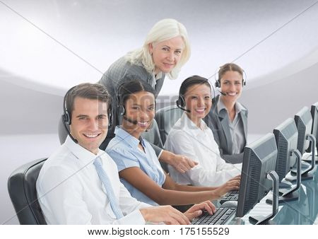 Portrait of smiling customer service peoples with headphones working on computer in office