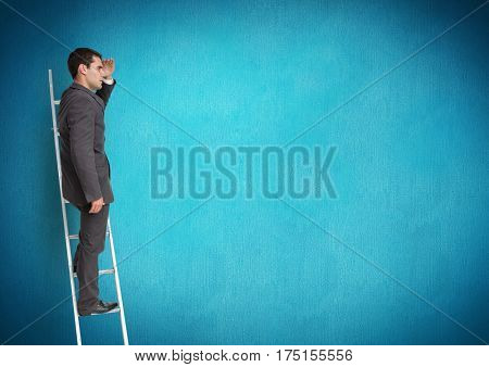 Businessman on ladder looking at a distance against blue background