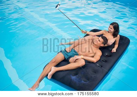 Smiling Couple Floating On Mattress In Pool And Taking Selfie Photo On The Phone With Selfie Stick O