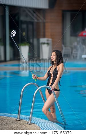 Attractive Female In A Black Bikini Posing Against Swimming Pool, Taking Selfie Photo With Selfie St