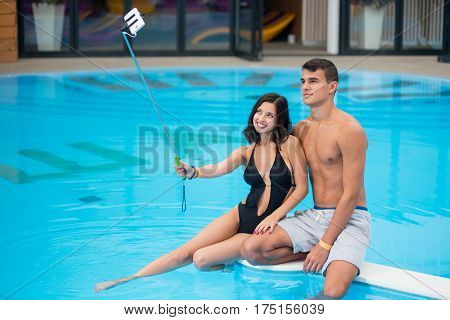 Young Couple Sitting On The Edge Of The Swimming Pool With Perfect Aqua Water And Taking Selfie Phot