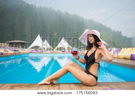 Young Tender Woman In A Hat And Black Bikini Sitting Next To Swimming Pool And Drinking Cocktail On