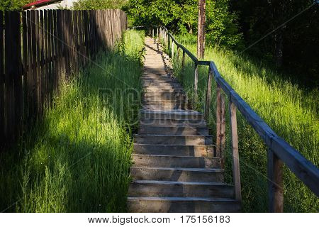 A wooden staircase rises up the mountain. Summer time. Green grass and staircase
