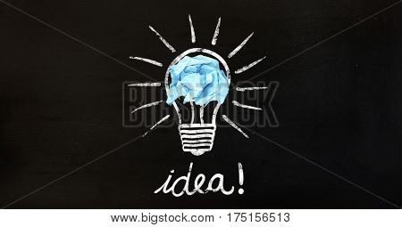 Conceptual image of bulb with crumpled paper and text idea on black background