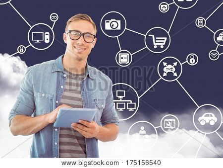 Man in spectacles holding digital tablet against digitally generated icons cloudy sky
