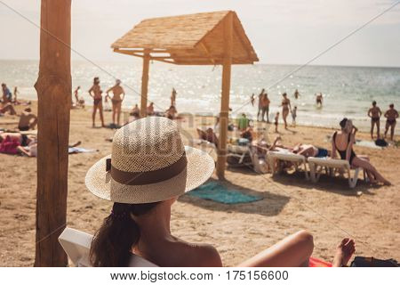 Woman in hat on beach. Blurred people near the sea. Good vacation place. Escape from problems and bustle.