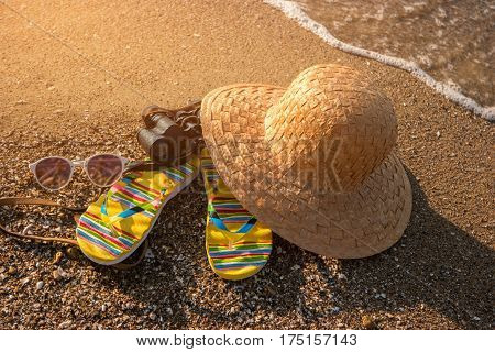 Beach hat on sand. Black vintage binoculars. New horizons await you. Get ready for adventures.