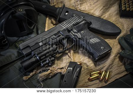 pistol 9mm and combat knife on fabric