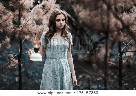 Very cute young girl lost with a kerosene lamp. Doll appearance. Woman with brown hair with lamp in a turquoise dress on nature. Long hair. Natural light. Model posing on the nature. Lamp in hand. Lost in forest