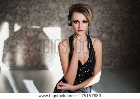 Lovely dj girl with tanned skin and white hair listening to music on headphones. Female dj beauty portrait of a beautiful makeup.  Dj enjoying good music