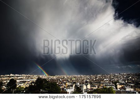 View of Paris from the hill of Montmartre. Travel through Europe. Attractions in France. Sunny Paris. Clouds in the sky. Double Rainbow. Thunder Sky above Paris