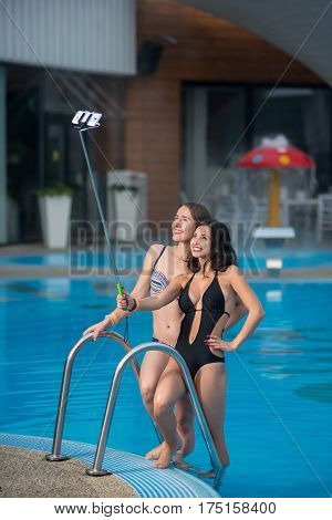 Two Happy Beautiful Girls In Swimsuits Posing Against The Swimming Pool With Perfect Aqua Water And