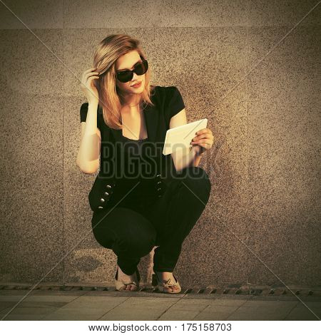 Young blond woman using tablet computer on city street. Stylish fashion model in sunglasses outdoor