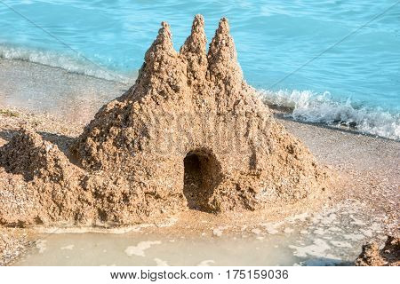 Sandcastle on seashore. Sand and blue water. Art is fragile. Welcome to the kingdom.