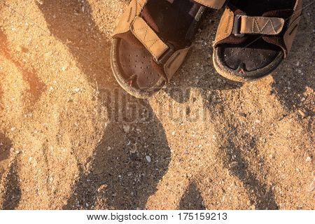 Sandals on sand background. Top view of footwear. Heat of tropical summer. Wander and explore the island.