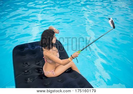 Profile Of A Young Brunette Makes Selfie Photo On The Phone With Selfie Stick On Mattress In Pool. C
