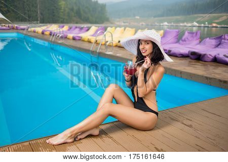 Attractive Smiling Woman In A Hat And Black Bikini Sitting With Cocktail On The Edge Of Swimming Poo