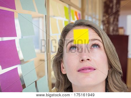 Digital composite image of female executive with sticky note on head in office