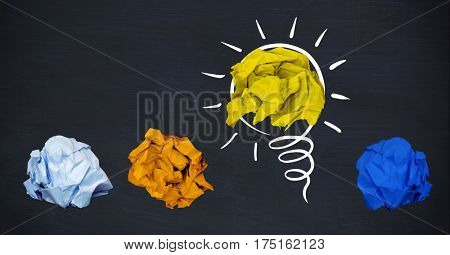 Conceptual image of colorful crumpled paper forming light bulb against black background