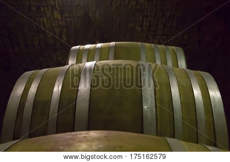 dark barrels from hard wood strapped with steel hoops stacked in a dark cellar winery