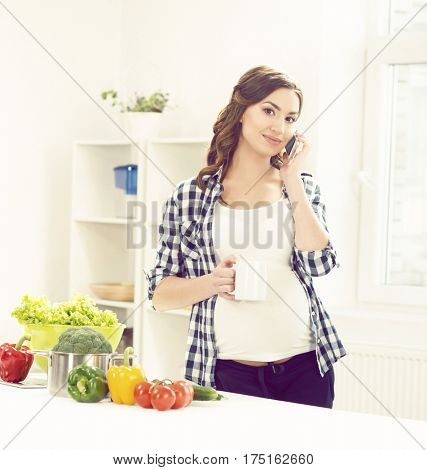 Beautiful pregnant woman with smartphone in kitchen. Motherhood, pregnancy, maternity concept.