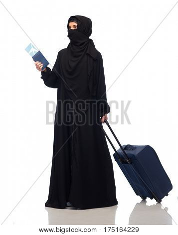 travel, tourism, flight and people concept - muslim woman in hijab with airplane ticket, passport and carry-on bag over white background