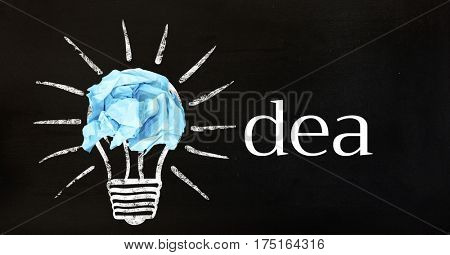 Digital composition of crumpled paper on light bulb shape with text idea against black background