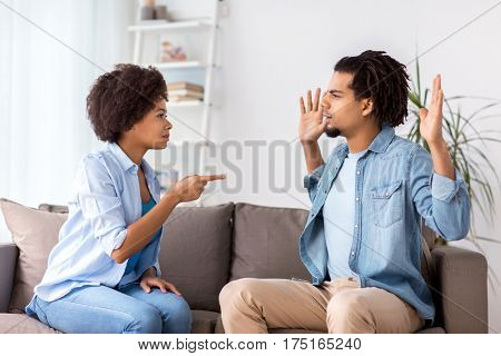 people, relationship difficulties, conflict and family concept - unhappy couple having argument and blaming each other at home