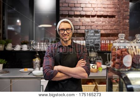 small business, people and service concept - happy seller man or barman at counter in vegan cafe or coffee shop