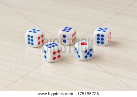 Five dice on a wooden table with shallow depth of field