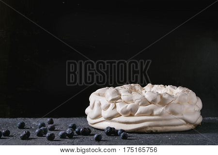 Homemade meringue basis for cake Pavlova with fresh blueberries on black concrete texture background. Copy space