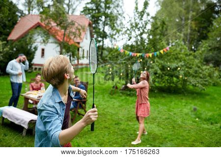 leisure, holidays, people and sport concept - happy friends playing badminton or shuttlecock at summer garden party