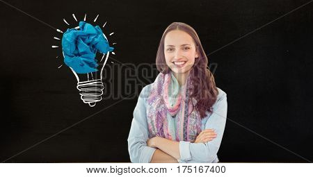 Digital composition of happy woman with crumbled paper on a drawn light bulb in background