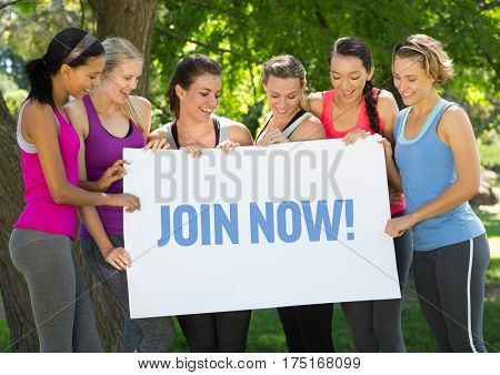 Group of happy women holding placard with text join now in park