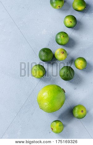 Whole lime and mini limes over gray stone texture background. Top view, space