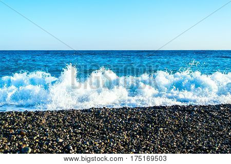 Sea waves breaking on a stony beach, forming sprays and splashes at sunset