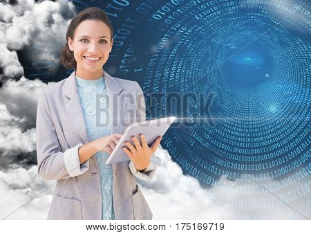 Digital composition of businesswoman holding digital tablet with binary codes and clouds in background