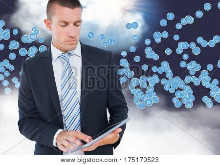 Digital composition of businessman using digital tablet against technology icons in sky