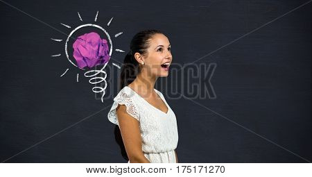 Cheerful woman standing next to light bulb with crumpled paper against black background